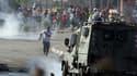Des manifestant palestiniens face à un véhicule de l'armée israélienne, près de la prison d'Ofer le 15 mai 2014.