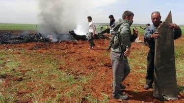 Des syriens armés vérifient les débris d'un avion abattu, une attaque revendiquée par un groupe rebelle allié à Al-Qaïda au dessus de la localité d'al-Eis le 5 avril 2016, dans le nord de la Syrie, une opération auparavant attribué aux j...