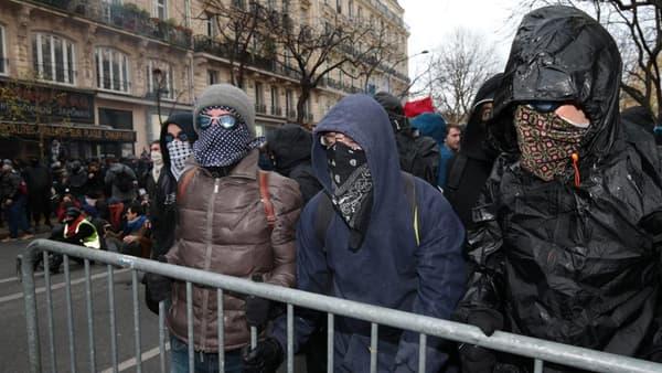 Des émeutiers masqués peu avant les affrontements avec la police, dimanche.