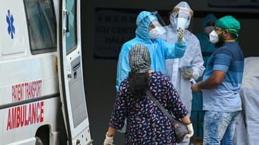 Des soignants et ambulanciers devant un centre de traitement du Covid-19, le 22 avril 2021 à Bombay, en Inde