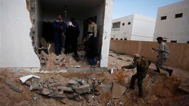 Insurgés libyens près d'une maison touchée par une frappe aérienne à Ras Lanouf, dans l'est de la Libye. Les forces gouvernementales ont poursuivi mardi leurs attaques contre les rebelles, dont les représentants politique ont de leur côté donné 72 heures
