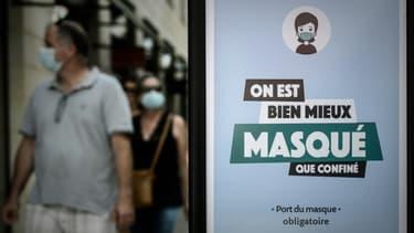 Un homme et une femme masqués passe devant une panneau d'information sur le port obligatoire du masque, le 18 juillet 2020 à Bordeaux