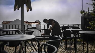 Un serveur disposant des tables sur une terrasse de Lisbonne au Portugal le 5 avril 2021.