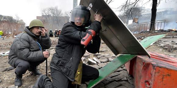 Des manifestants se protègent des tirs d'un sniper, à Kiev, jeudi.