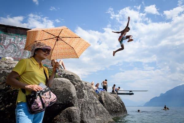 Un garçon en train de plonger dans le lac de Genève en Suisse, tandis  qu'une femme se protège du soleil à laide d'une ombrelle le 31 juillet dernier.