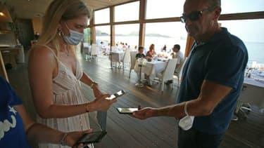 Vérification du pass sanitaire à l'entrée d'un restaurant le 23 juillet 2021 à l'Ile Rousse, en Corse