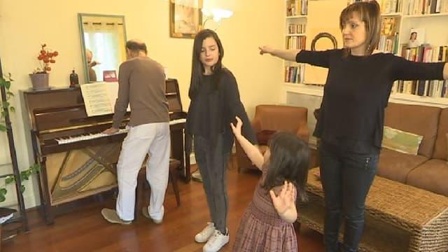 Avec leur maman, Ines et Daphnée font l'exercice de sophrologie de l''arbre.