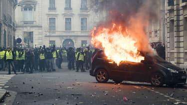 Une voiture en feu, dans le quartier des Champs-Elysées, à Paris, le 8 décembre 2018, en marge d'une manifestation des gilets jaunes