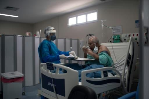Un infirmière apporte un plateau à un malade du Covid dans un hôpital de Marica City, dans l'état de Rioo au Brésil, le 5 juin 2020.