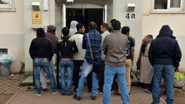Des réfugiés font la queue devant un centre d'enregistrement de demandes d'asile