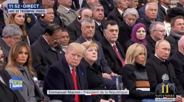 Le président du Kosovo, coupe de cheveux en brosse, cheveux gris, au deuxième rang derrière Brigitte Macron et Vladimir Poutine.