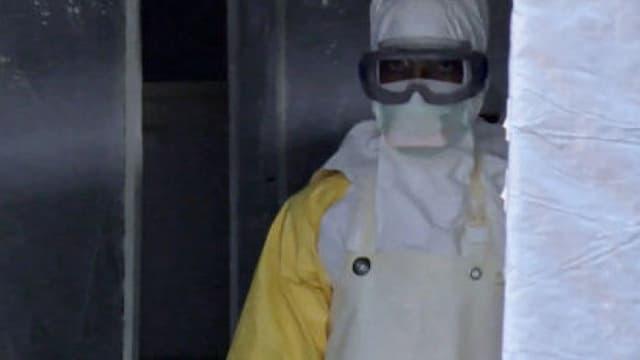 Homme portant un masque et une combinaison à l'entrée d'une tente médicale à Gueckedou, en Guinée (photo d'illustration).