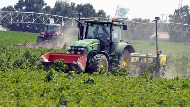 Un tracteur portant le drapeau du syndicat de la FNSEA détruit un champ de cultures OGM en 2014.