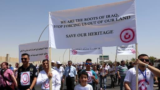 """Lors d'une manifestation anti Etat islamique, les manifestants brandissent le """"n"""" arabe dont les jihadistes se servent pour marquer les maisons chrétiennes."""