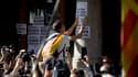 """Un manifestant pro-indépendance colle des affiches pendant une démonstration de force des partisans du """"oui"""", le 20 septembre, à Barcelone."""