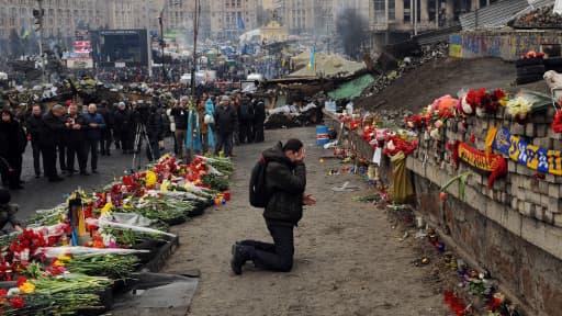Un homme pleure devant un mémorial commémorant les manifestants tués pendant les violences en Ukraine, le 23 février 2014.