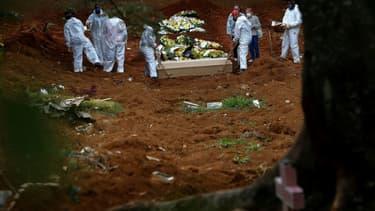 Un cercueil avec la dépouille d'une personne décédée du Covid-19 est mis en terre au cimetière de Vila Formosa, à Sao Paulo, au Brésil, le 14 avril 2021