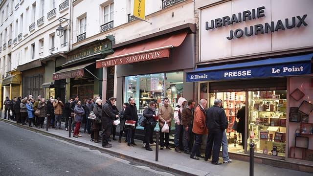 """Le 14 janvier, des gens font la queue devant une librairie pour se procurer le dernier exemplaire de """"Charlie Hebdo""""."""