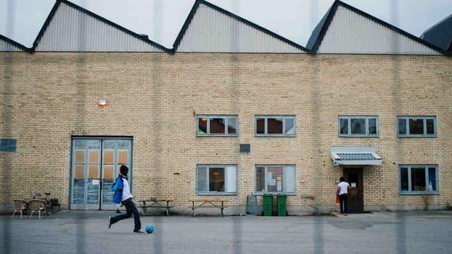 Un enfant joue au ballon devant un centre de réfugiés dans la banlieue de Stockholm.