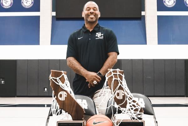 Andre Chevalier, coach de l'équipe de basket de Sierra Canyon, pose avec les titres de champion d'Etat 2018 et 2019