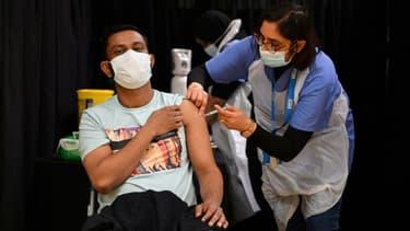 Un homme se fait injecter une dose du vaccin d'AstraZeneca, à Londres le 14 avril 2021
