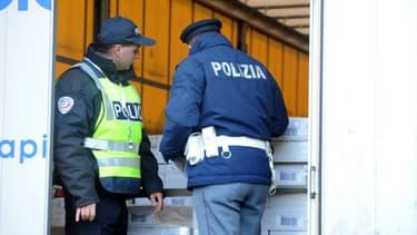 Deux policiers vérifient un camion à la recherche d'éventuels clandestins entre la France et l'Italie (image d'illustration)
