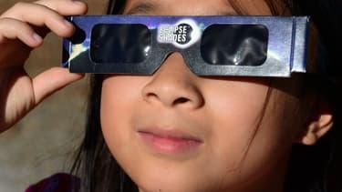 Une jeune fille portant des lunettes de protection lors d'une éclipse de soleil sur les monts San Gabriel, Los Angeles
