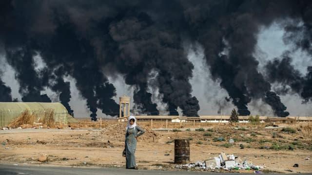 Pour limiter la visibilité des frappes aériennes turques, les forces kurdes allument des feux qui font des panaches de fumée noire, près de la ville de Ras al-Ain
