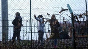 Des migrants marchent le long des rails sur le site de Calais-Frethun.