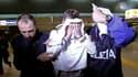 Un homme (au centre), qui souhaitait détourner vers la Libye un vol Paris-Rome d'Alitalia dimanche, a été maitrisé par l'équipage et des passagers avant d'être arrêté à sa descente d'avion. /Photo prise le 25 avril 2011/REUTERS/Alessandro Bianchi