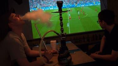 Fumeurs de chicha devant un match de football