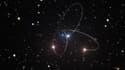 Vue d'artiste représentant les orbites de trois étoiles proches d'un trou noir au milieu de la Voie Lactée.