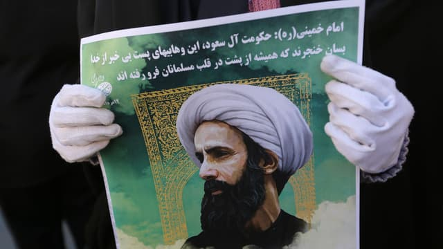 Une Iranienne brandit le portrait du dignitaire chiite exécuté en Arabie saoudite lors d'une manifestation à Téhéran