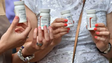 Des patients tiennent des flacons vides de médicaments lors d'une marche symbolique pour le traitement du SIDA devant le cabinet des ministres à Kiev, le 1er juin 2015 (illustration)