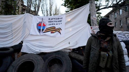 Un militant pro-russe vendredi devant le siège des services spéciaux à Slaviansk, bastion des insurgés dans l'Est de l'Ukraine.