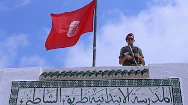 Un membre de la Garde nationale tunisienne surveille un bureau de vote, à Sousse (PHOTO D'ILLUSTRATION)