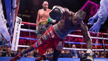 Tyson Fury (arrière-plan) inflige un KO à Deontay Wilder lors de leur troisième combat en octobre 2021
