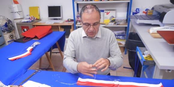 Patrick Varinard à l'oeuvre. L'ensemble de l'assemblage d'une écharpe tricolore est réalisé à la main.