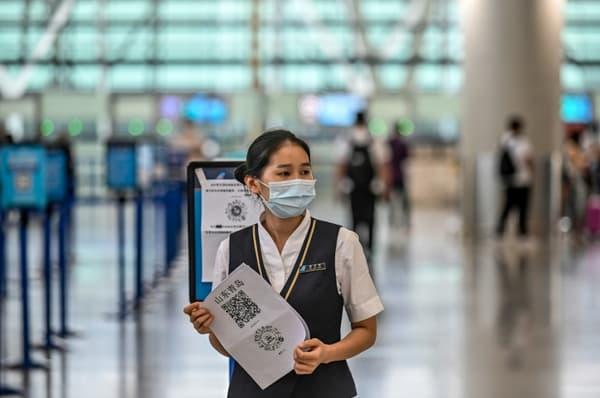 Une employée de l'aéroport de Shanghai-Pudong tient un QR code pour vérifier l'état de santé des voyageurs, le 11 juin 2020 en Chine