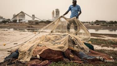 Un pêcheur trie ses filets devant la cimenterie SOCOCIM, le long du littoral à Bargny, au Sénégal, le 16 juin 2020.
