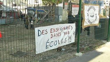 """Derrière ces grilles à Saint-Denis, le terrain vague où le """"Ministère des bonnets d'âne"""", collectif de parents d'élèves du 93 en colère, a pris ses quartiers."""