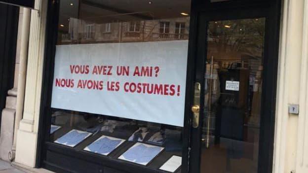La pancarte parodique, dans la vitrine d'un magasin de costumes, à Paris.