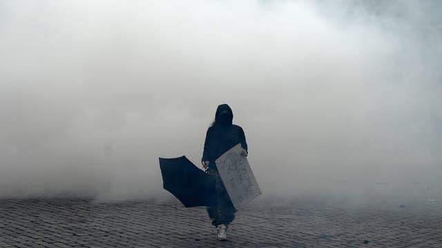 Une manifestante marche devant des gazs lacrymogènes à Place d'Italie, à Paris, le 16 novembre 2019