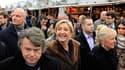 """Marine Le Pen accompagnée du président de son comité de soutien, l'avocat Gilbert Collard, sur le marché de Noël des Champs-Elysées. Dénonçant """"l'incohérence"""" des Verts, la candidate du Front national à l'élection présidentielle s'est posée lundi en chant"""