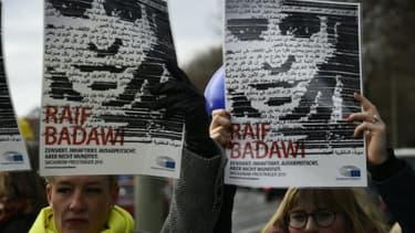 Des membres de l'ONG Amnesty International brandissent des portraits du blogueur saoudien Raef Badawi lors d'une manifestation devant l'ambassade d'Arabie saoudite à Berlin, le 8 janvier 2016.