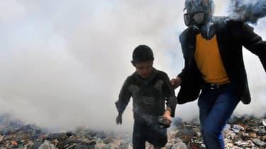 Un homme portant un masque à gaz escorte un enfant dans une rue enfumée d'Alep, en Syrie, le 24 mars 2013. (photo d'illustration)