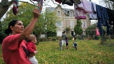 Une femme d'une famille Kosovare, réfugiée et demandeuse d'asile étend le linge, en 2009 en banlieue d'Angers, dans le jardin du pavillon qu'ils squattent faute de pouvoir bénéficier de places d'hébergement