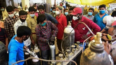 Des gens remplissent des bouteilles d'oxygène médical pour les patients atteints du coronavirus Covid-19 dans une station de remplissage d'oxygène à Allahabad (Inde) le 20 avril 2021.