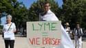 """Une femme tient un panneau """"Lyme=vie brisée""""."""