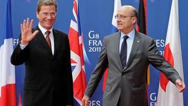 Le ministre des Affaires étrangères Alain Juppé aux côtés de son homologue allemand Guido Westerwelle, lors d'une réunion des chefs de la diplomatie du G8, à Paris. Dans un projet de déclaration obtenu par Reuters, le G8 menace Mouammar Kadhafi de conséqu